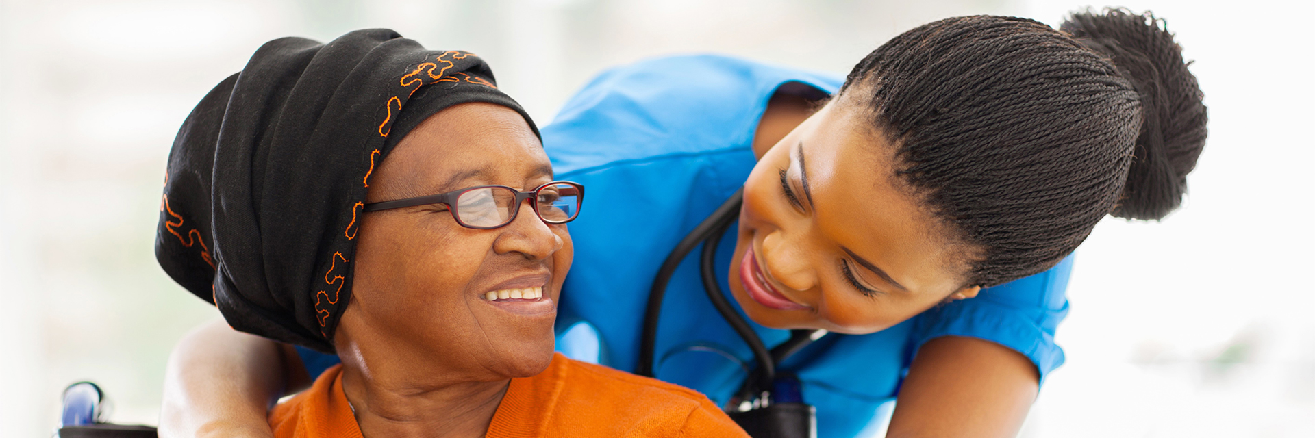 nurse in blue scrubs hugging woman in orange top